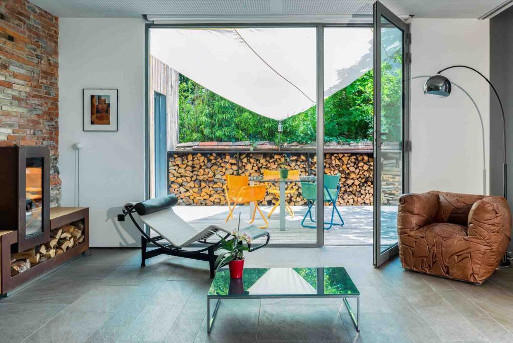 Salon de la maison passive de Seuil architecture, avec son poêle à bois et son bûcher