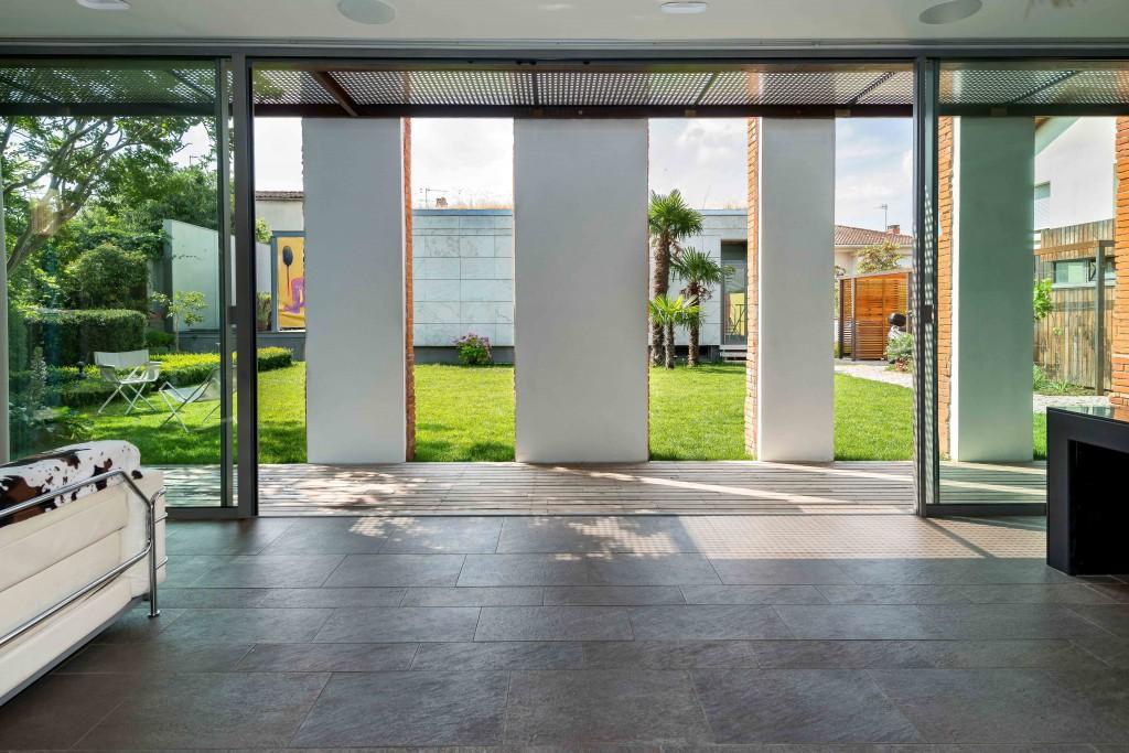 Les meneaux de la maison passive séquencent les vues vers l'agence Seuil architecture en second plan.